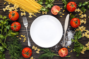 Table setting with cutlery, pasta, tomatoes and herb on dark wooden table.