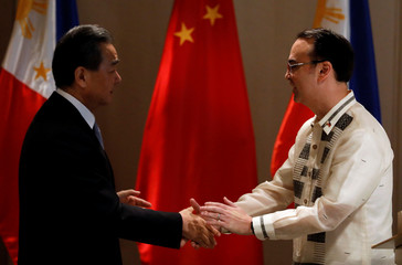 Philippine Foreign Affairs Secretary Alan Peter Cayetano shakes hands with China's Foreign Minister Wang Yi in Taguig
