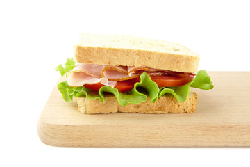 Sandwich with lettuce,tomato,cold cuts on cutting board on white