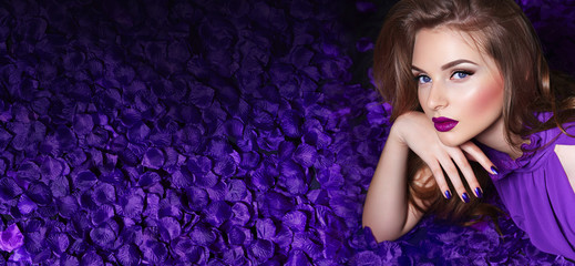 The girl in the petals. Beautiful young girl lies in the violet petals in a long dress. Glamor,...