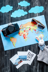 accessories for treveling with children, camera, map and photos on dark woode background top view mock-up