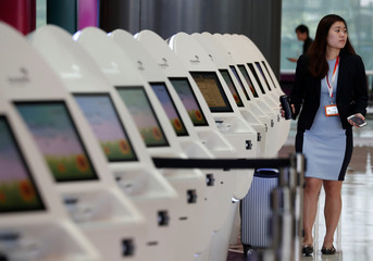 A woman stands near a row of self check-in counters at the departure hall during a media tour of Changi Airport Terminal 4 in Singapore