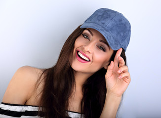 Beautiful smiling young make-up model with brown hair posing and holding the blue baseball cap. Closeup portrait