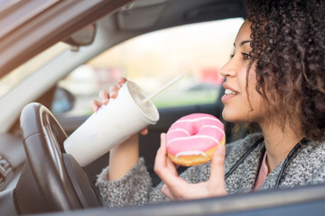 Woman eating a sweet and drinking driving a car