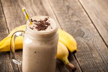 Banana chocolate smoothie and banana on wooden table