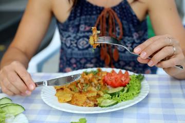Frau isst im Restaurant ein Gericht mit Pfifferlingen  im Sommer