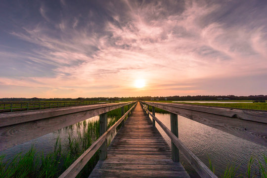 boardwalk leading into the marsh of the Atlantic Ocean coast during a beautiful evening and sunset with an expressive sky