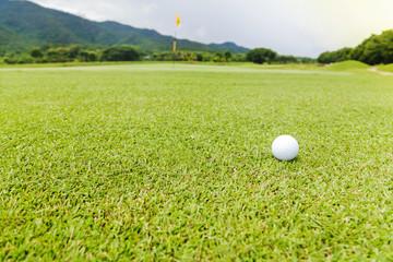 Golf ball on green grass on golf course