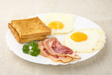 Slice of bacon with two eggs on the plate with toasts