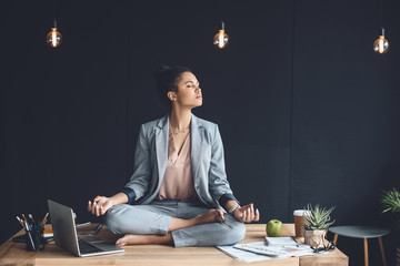 african american businesswoman sitting in lotus pose on table while meditating in office Wall mural