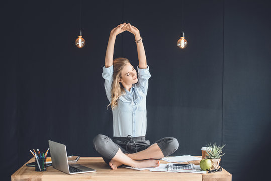 businesswoman sitting in lotus position on table with laptop in office