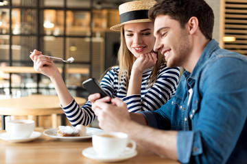portrait of young couple using smartphone while sitting together in cafe