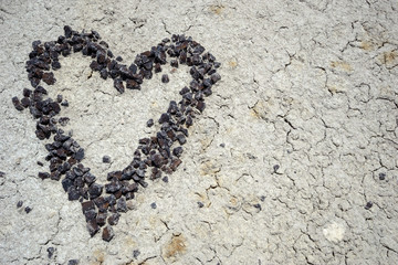 stone heart made of reddish pebbles on the dry ground of a rock desert