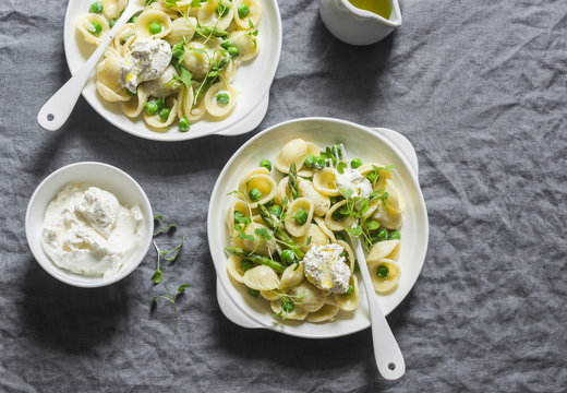 Pasta with green peas, asparagus and fresh ricotta. On a gray background, top view. Healthy delicious food