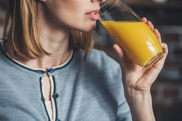 Portrait of young woman drinking orange juice, cropped image