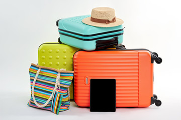 Summer luggage, accessories, tablet. Suitcases, clothes on white background.