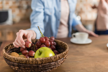 Cropped image of woman taking grapes from basket on kitchen table
