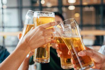 Close-up cropped image of friends clinking with beer in cafe