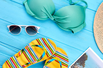 Woman beach accessories close up. Colorful bra, sandals, glasses, panama, picture.