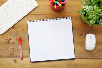 Blank notebook paper, keyboard, mouse and pens on wood table background