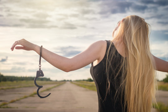 A beautiful married model girl with long hair with handcuffs on her hands is walking along an empty road to meet freedom. Family Violence