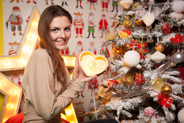 Young beautiful girl in the New Year decorations on the background of wallpaper with colorful people