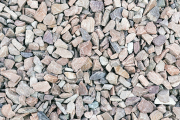 Small rock crushed stone road-metal. Pile of white, grey and yellow rocks. Road-metal background