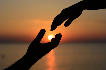 A man holds the sun in his hands and gives it to his beloved girl. Love and romance.