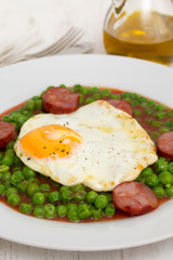 peas with smoked sausage and fried egg on plate