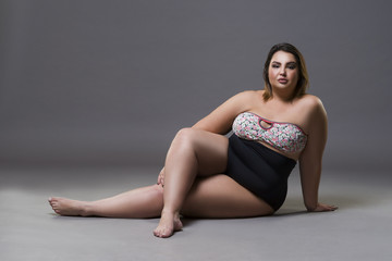 Plus size fashion model in sexy swimsuit, young fat woman on gray background, overweight female body