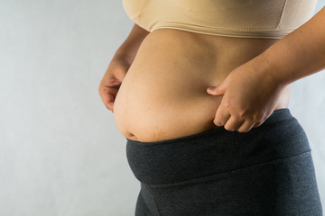 woman's hand holding excessive belly fat