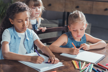 little girl looking how friends drawing pictures with colorful markers at home