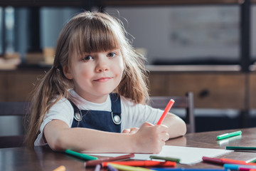 portrait of cute smiling girl sitting at table and drawing picture at home