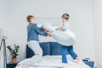 little boys in pajamas jumping on bed and having pillow fight at home