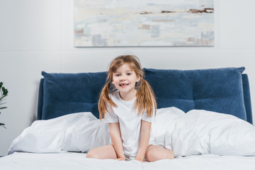portrait of smiling little girl in pajamas sitting on bed and looking at camera