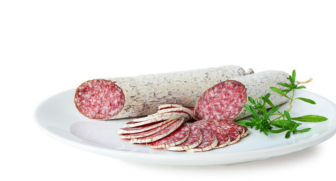 Winter salami sticks and slices on white plate isolated