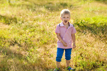 A boy play with water sprinkler in the summer garden