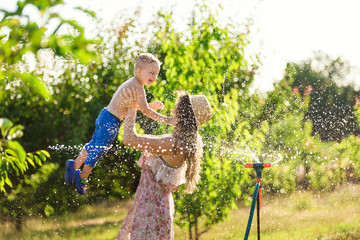 a mother and a son play with water sprinkler in the garden