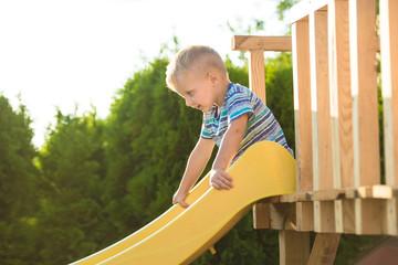 A boy on the play ground. Children slide