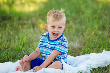 Very cheerful little boy in the garden