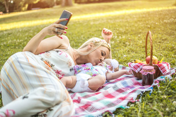 Mother kissing her baby and taking a selfie photo on mobile phone in the park.