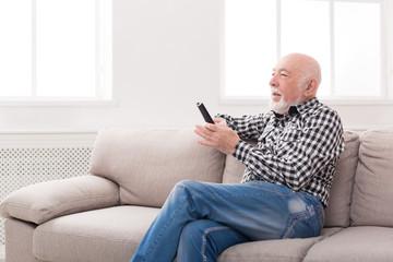 Emotional senior man watching tv copy space
