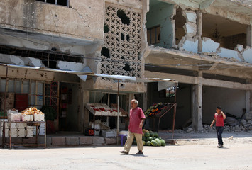 People walk past a fruit and vegetable shop in Deraa