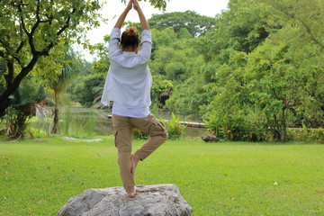 Young man practicing yoga meditation on the rock in beautiful outdoor park.