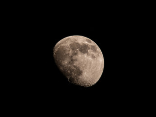 The moon against a black sky, waxing gibbous 82%. Taken in Thailand