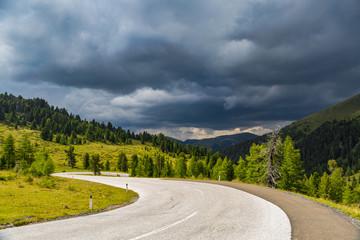 kurvenreiche Straße in den Alpen mit Gewitterwolken