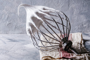 Process of cooking meringue. Whipped egg whites on mixer whisk on linen towel over gray texture background. Baking dessert concept. Close up