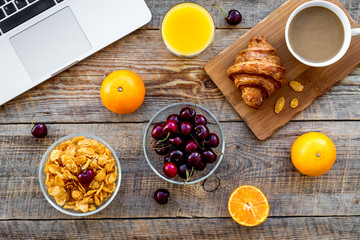 Summer breakfast in front computer. Muesli, fruits, croissant, coffee on wooden table background top view