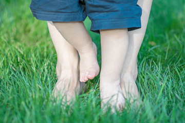 baby and mother feet walking on grass. The fiest steps of child