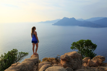 Fotomurales - Young woman looking over the sea from the rocks near the famous Chateau Fort. Corsica, France.